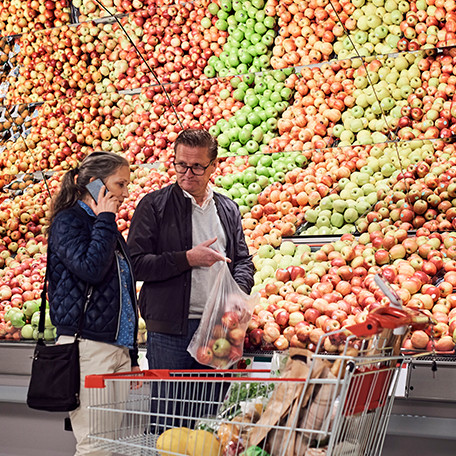 Shoppers in the grocery store next to a variety of apples